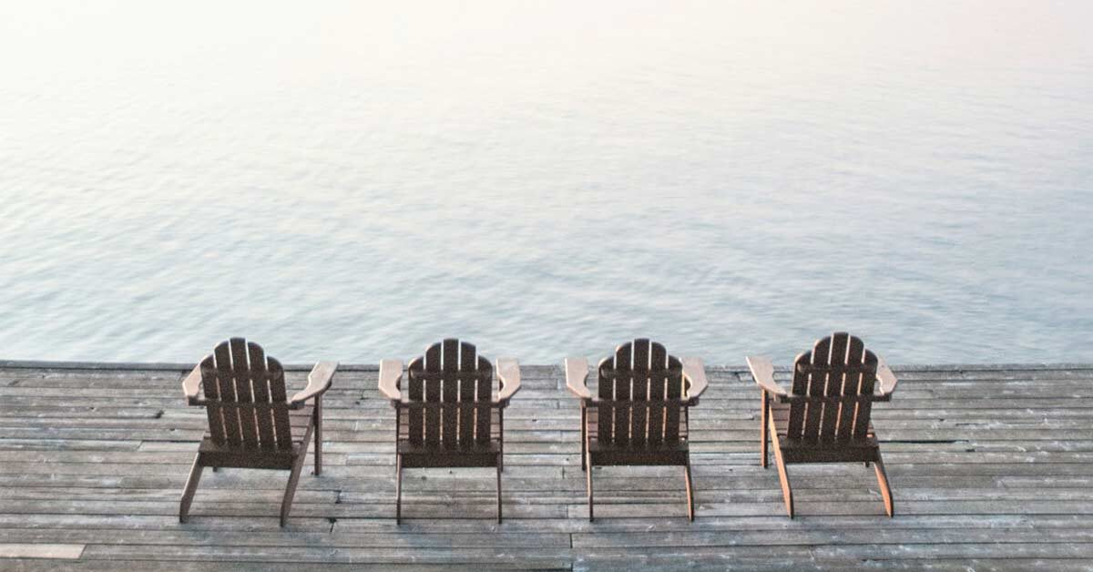 Four empty chairs on lake dock waiting for someone to enjoy a slow day.