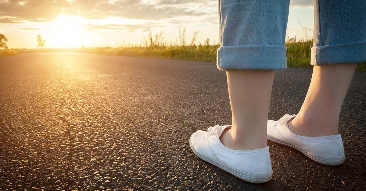 Woman standing on road watching the sunrise as she prepares to start slow on her morning walk.
